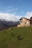 小山的偏僻的石房子在多雪的山背景,垂直 免版税库存图片