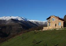 小山的偏僻的石房子在多雪的山背景,明白蓝天,水平 免版税库存图片