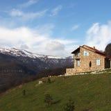 小山的偏僻的石房子在多雪的山背景,正方形 库存照片