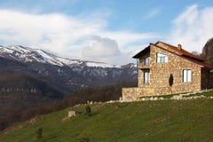 小山的偏僻的石房子在多雪的山背景,水平 免版税图库摄影