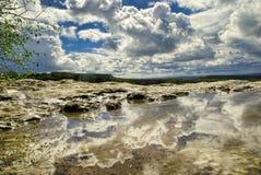 小山的反射 山和天空在水坑 免版税库存照片