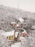 小山的底部的积雪的房子 图库摄影