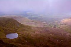从小山的看法在神秘的湖Llyn在笔y爱好者峰顶附近的Cwm Llwch,布雷肯比肯斯山,威尔士,英国 免版税图库摄影