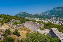 从小山的被破坏的堡垒墙壁和Sutomore镇视图 库存图片