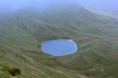小山的(Llyn Cwm Llwch)一个暗藏的不可思议的被迷惑的湖在笔y爱好者峰顶,布雷肯比肯斯山,威尔士,英国附近 免版税库存照片