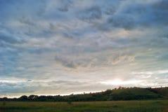 小山萨拉托夫地区的领域和草甸在蓝色多云天空下 免版税库存图片