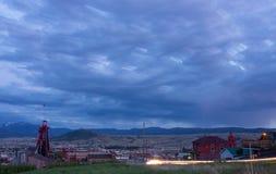 小山蒙大拿与开采的井塔的夜都市风景 库存图片