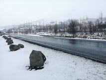 小山路风景在冰岛的冬天 柏油路以斜向一边有很多雪 免版税图库摄影
