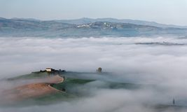 小山顶农舍&柏树鸟瞰图在托斯卡纳在一个有雾的春天早晨 免版税库存图片