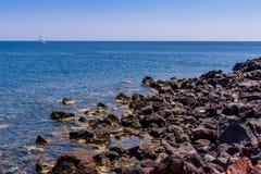 小岩石、海和yatch,santorini海岛,希腊 免版税库存图片