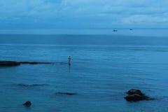 小岩石的孤独的渔夫 图库摄影