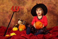小巫婆获得乐趣为万圣夜用南瓜和帽子 免版税库存图片