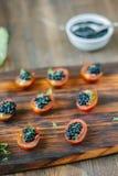 小开胃菜用西红柿和黑鱼子酱 免版税库存图片