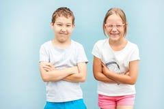 小弟弟和姐妹孪生站立与滑稽的面孔的8岁 免版税图库摄影