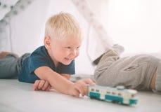 小弟弟在地板放置 男孩在家充当有玩具汽车的家早晨 偶然生活方式 免版税库存照片