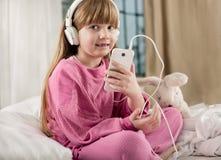 小微笑的女孩在床上听音乐 免版税库存图片