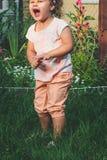小微笑的女孩在庭院里,夏令时 免版税库存图片