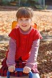 小微笑的女孩坐木跷跷板 库存照片