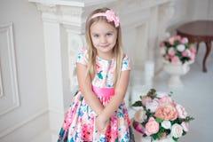小微笑的女孩孩子画象五颜六色礼服摆在的室内 库存照片