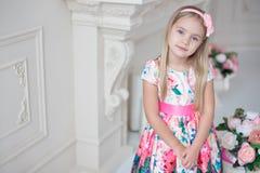 小微笑的女孩孩子画象五颜六色礼服摆在的室内 免版税库存图片