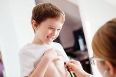 小微笑的男孩孩子由医生审查 免版税库存图片
