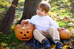 小微笑的男孩用二个万圣节南瓜 图库摄影