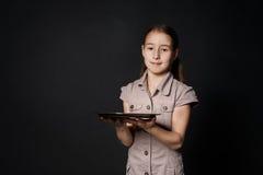 小微笑的白种人女孩拿着空的食物盘子 库存图片