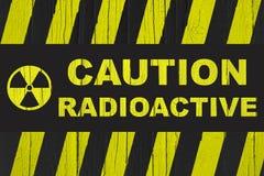 `小心、放射性在与辐射标志的大胆的信件中写道的`警报信号和黄色和黑条纹 免版税图库摄影