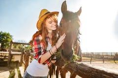 小心和拥抱的微笑的妇女女牛仔她的马 库存图片