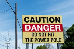 小心在电源杆附近的危险标志 免版税库存照片