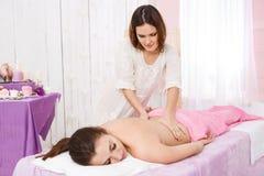 小心地小心地做在妇女的女性男按摩师按摩,看下来 免版税库存图片