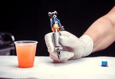 小心地拿着纹身花刺设备的tattooer的手 免版税图库摄影