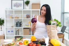 小心地看和拿着圆白菜的主妇的正面图画象,选择好新鲜的成份为她的维生素 免版税库存图片