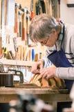 小心地雕刻琵琶的形状的Luthier 免版税库存照片