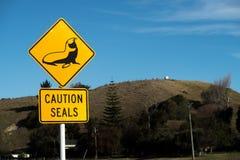 小心封印路标沿沿海路是典型的在新西兰 免版税库存照片