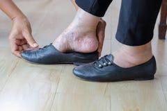 小心投入在鞋子送礼者的年长妇女 免版税库存照片