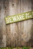 小心有狗在老被佩带的木篱芭的标志 免版税库存照片