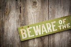 小心有狗在老被佩带的木篱芭的标志 免版税库存图片