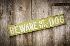 小心有狗在老被佩带的木篱芭的标志 库存照片