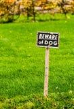 小心有狗标志张贴了到在绿色领域的老,被风化的木岗位 免版税库存照片
