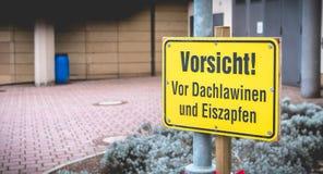 小心!在屋顶雪崩和冰柱前面用德语 库存图片