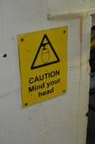 小心头脑您的顶头标志 库存照片