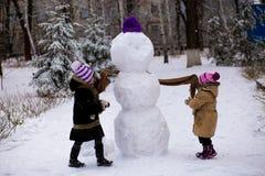 小快乐的女孩穿上了一个大雪人的一条围巾 库存照片