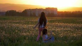 小快乐的姐妹有乐趣户外戏剧吉他跳舞和跳在户外 蒲公英调遣在日落,时间, 影视素材