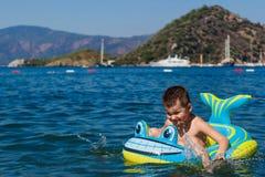 小快乐的婴孩在一条可膨胀的小船的海漂浮鲨鱼 免版税库存照片