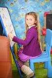小愉快的女孩使用与磁铁在儿童居室。 免版税库存图片