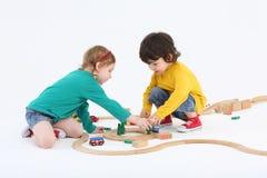 小愉快的女孩和男孩在木铁路附近安排树 免版税库存图片