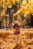 小愉快的女孩投掷下落的叶子 免版税库存图片