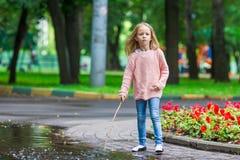 小愉快的女孩获得乐趣在一个大水坑  库存照片