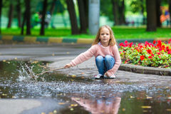 小愉快的女孩获得乐趣在一个大水坑  免版税库存图片